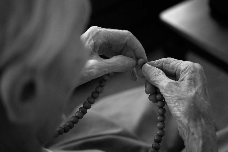 Cropped Image Of Senior Woman Praying Rosary Beads At Home