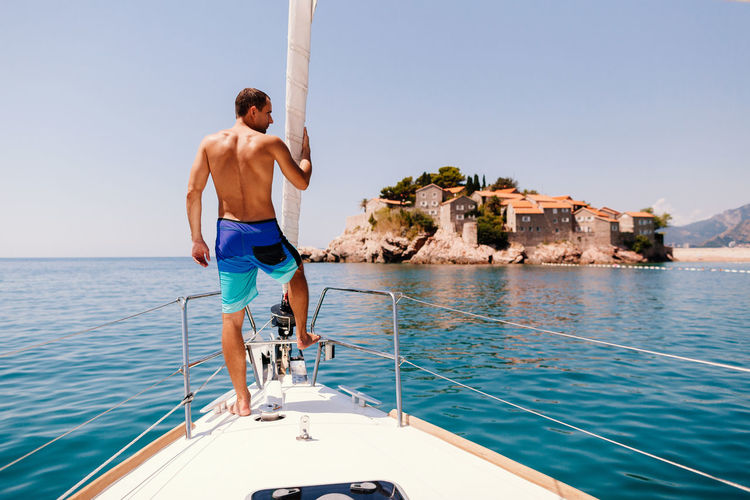 Full Length Rear View Of Shirtless Man Standing On Yacht Sailing On Sea