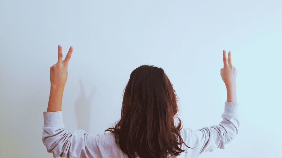 Rear view of girl gesturing peace sign while standing by wall