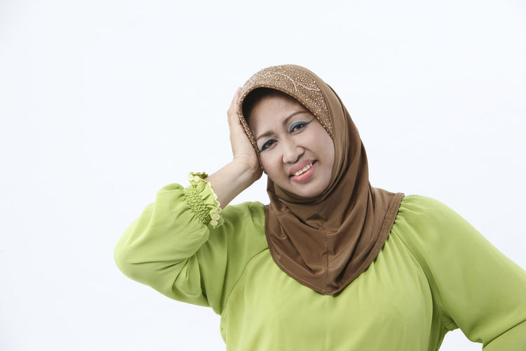 mature malay woman with tudung on white background Asian  Isolated Muslimah Standing Casual Clothing Cut Out Depression - Sadness Facial Expression Front View Hand On Head Headache Headwear Looking At Camera Malay Ethnicity Mature Adult Mature Women One Person Portrait Real People Scarf Sick Studio Shot Tudung Waist Up White Background