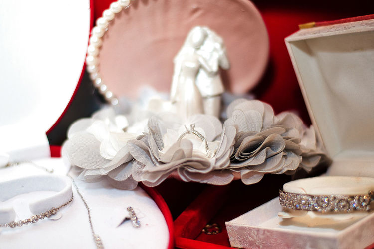 Close-up of wedding figurines and jewelry on table