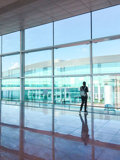 Young casual female traveler at airport, looking through the airport gate windows Glass - Material Real People One Person Transparent Built Structure Reflection Full Length Architecture Window Indoors  Day Flooring Building Lifestyles Standing Walking Airport Modern Office Building Exterior Tiled Floor Terminal Architecture Minimalism Travel Destinations Traveling