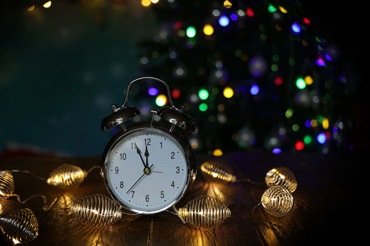 Close-up of illuminated christmas lights and clock on table
