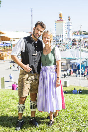 A young couple pose in front of the camera at the Octoberfest festival in Munich, Germany. The couple are wearing the traditional clothing from the festival, lederhosen and dirndl Bonding Couple - Relationship Day Dirndl Focus On Foreground Front View Full Length Happiness Heterosexual Couple Lederhosen Leisure Activity Lifestyles Looking At Camera Love Octoberfest Outdoors Portrait Real People Smiling Standing Togetherness Two People Young Adult Young Men Young Women
