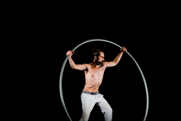 Circus Adult Arms Raised Black Background Copy Space Front View Holding Human Arm Indoors  Men Muscular Build One Person Performance Plastic Hoop Shirtless Skill  Standing Strength Studio Shot Three Quarter Length Young Adult Young Men