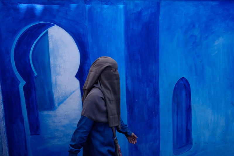 Woman wearing a niqab walks in front of a blue painted mural in ancient medina. chefchaouen. morocco