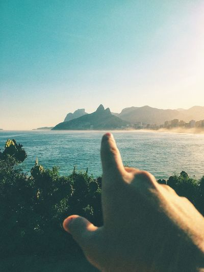Cropped Image Of Man Pointing At Mountain By Sea Against Sky