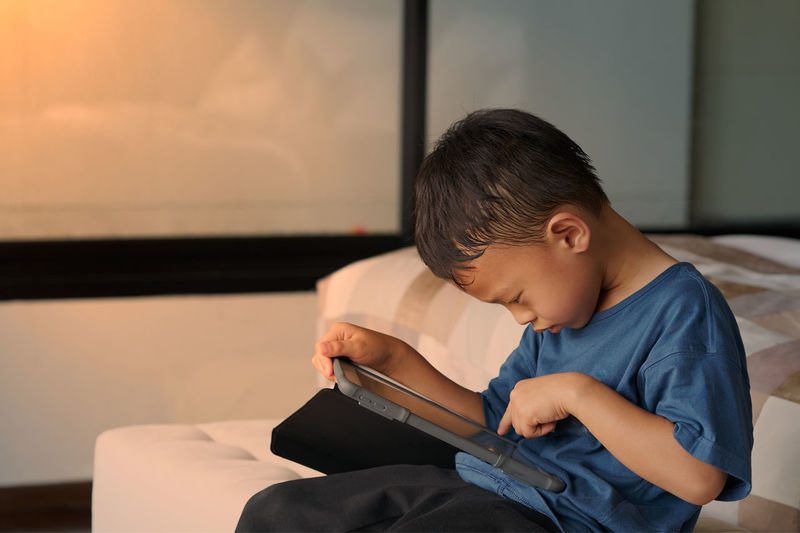 Boy using digital tablet while sitting on bed at home