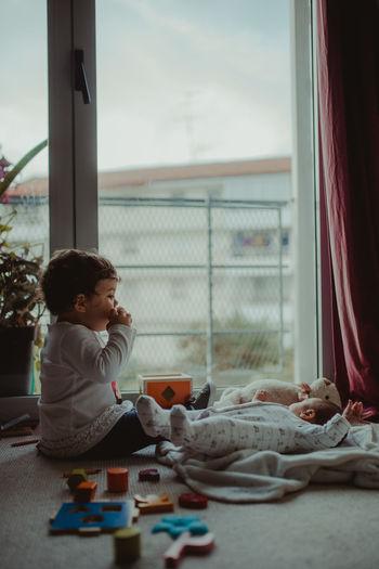 Baby siblings sitting at home