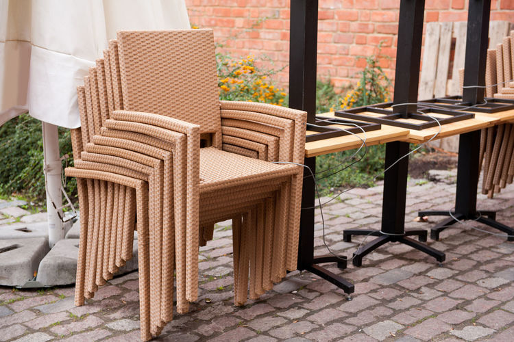 Plastic chairs set and tables one on another, binded with cable, waiting for clients, Warsaw, Poland. Armchair Armchairs Bind Binded Chair Chairs Heap No People Outdoors Outside Paving Stone Plastic Restaurant Seats Stack Table Tables Tether Tethered Tied Tourism Truss