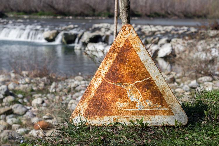 Abandoned information sign against river