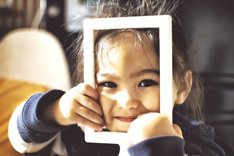 Portrait Of Smiling Girl With Photo Frame