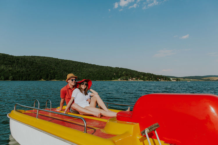 Cheerful man and woman having fun boating on the lake. Portrait of couple in love relaxing on pedal boat on warm sunny day. Boating Couple Holiday Hot Day Love Summertime Vacations Young Boat Boyfriend Caucasian Feet Girlfriend Lake Outdoors Pedalo Relax Resting River Sea Summer Sunglasses Sunhat Two People Water