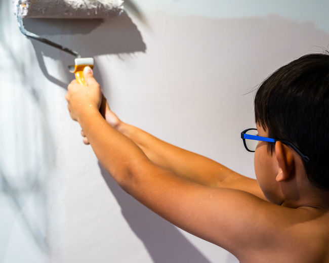 Repair in the apartment. happy child shirtless asian boy paints the wall with pastel pink paint.