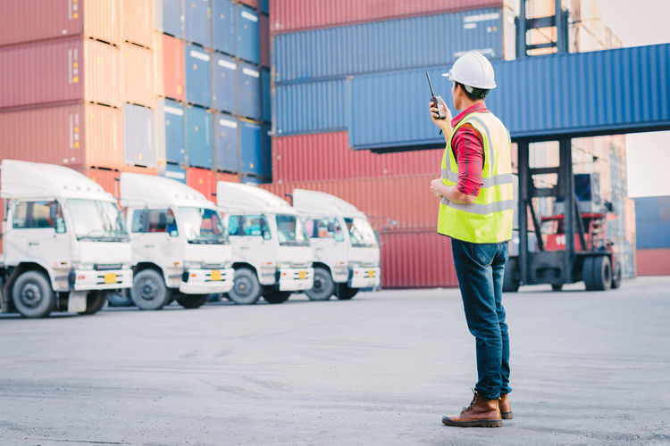 Full length of manual worker using walkie-talkie at commercial dock