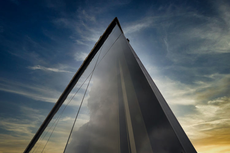 Low angle view of glass structure against sky