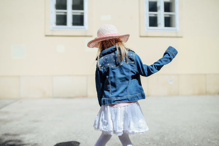 One Person Clothing Real People Child Leisure Activity Hat Focus On Foreground Three Quarter Length Childhood Girls Lifestyles Females Standing Day Building Casual Clothing Outdoors Obscured Face Innocence White Skirt Jeans Jeans Jacket Daylight Sunshine