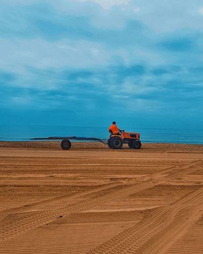Toy car on desert land against sky