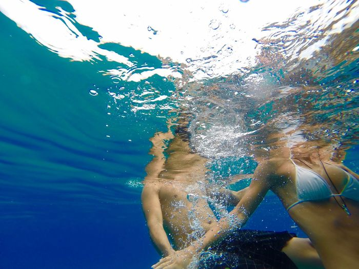 Midsection of friends swimming in sea