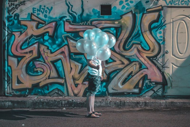 Side view of woman holding balloons over face while standing against graffiti wall