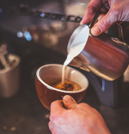 Cropped hands of person pouring milk in coffee cup