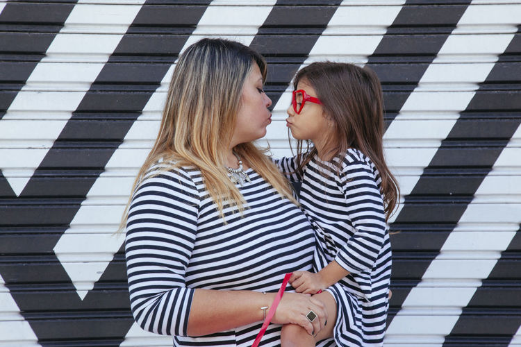 Woman carrying daughter while standing by wall