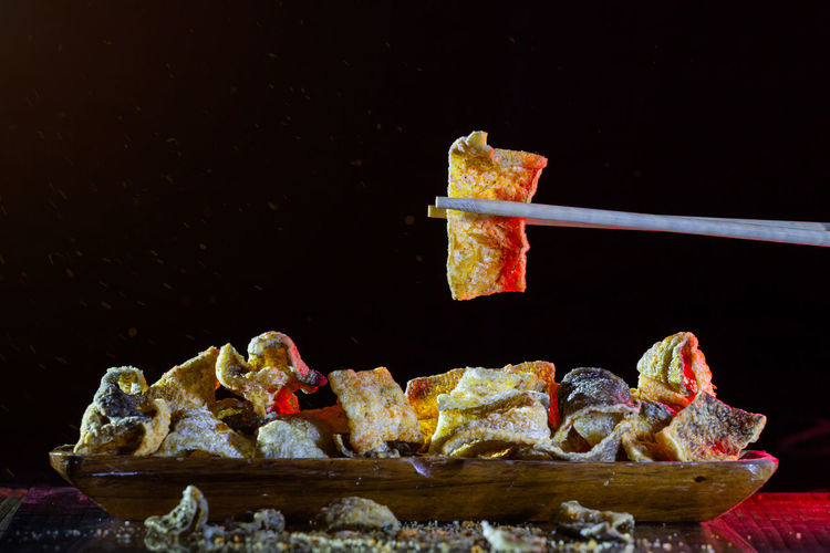 Close-up of meat on barbecue grill against black background