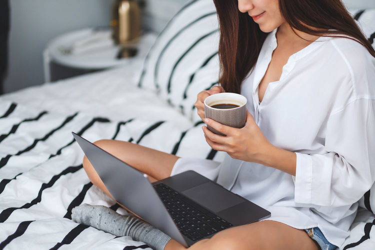 Midsection of woman holding coffee cup sitting on bed