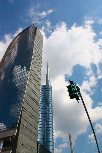 Low angle view of modern buildings against cloudy sky