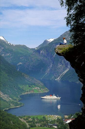 Woman sitting on cliff against mountain range