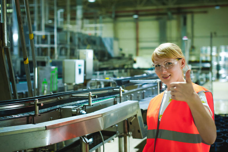 Portrait Of Woman In Protective Eyewear Gesturing At Factory