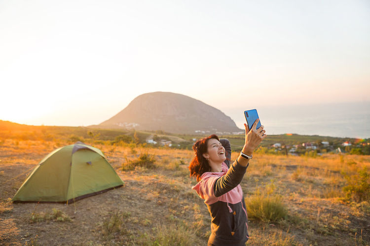 Woman takes photos of the sunrise in the mountains on her phone. selfie in rising sun. panoramic