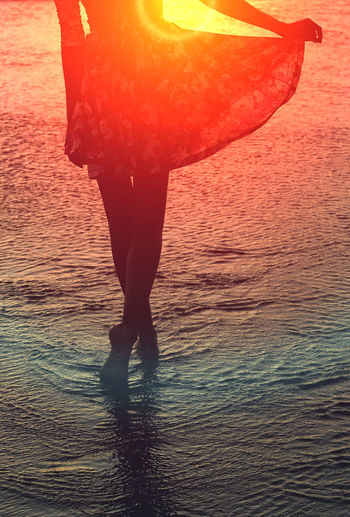 Low section of woman standing on beach during sunset