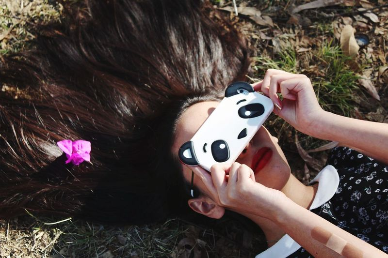 Woman covering eyes with mobile phone on field