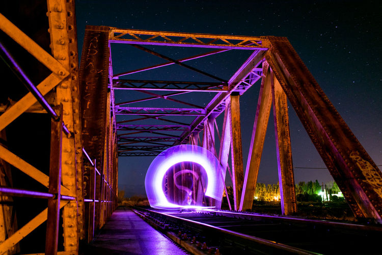 Illuminated railroad bridge at night