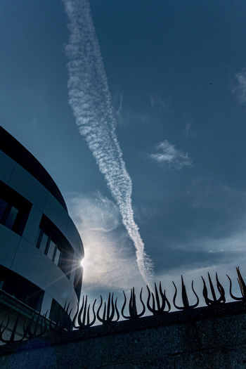 Sky Built Structure Architecture Building Exterior Cloud - Sky No People Nature Transportation Motion Low Angle View Vapor Trail Outdoors Mode Of Transportation Day Air Vehicle Blue Building Communication City Long Exposure