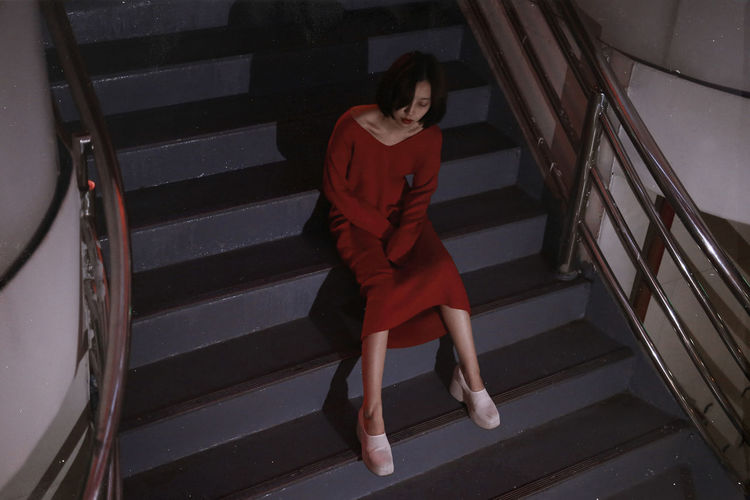High Angle View Of Young Woman Sitting On Steps