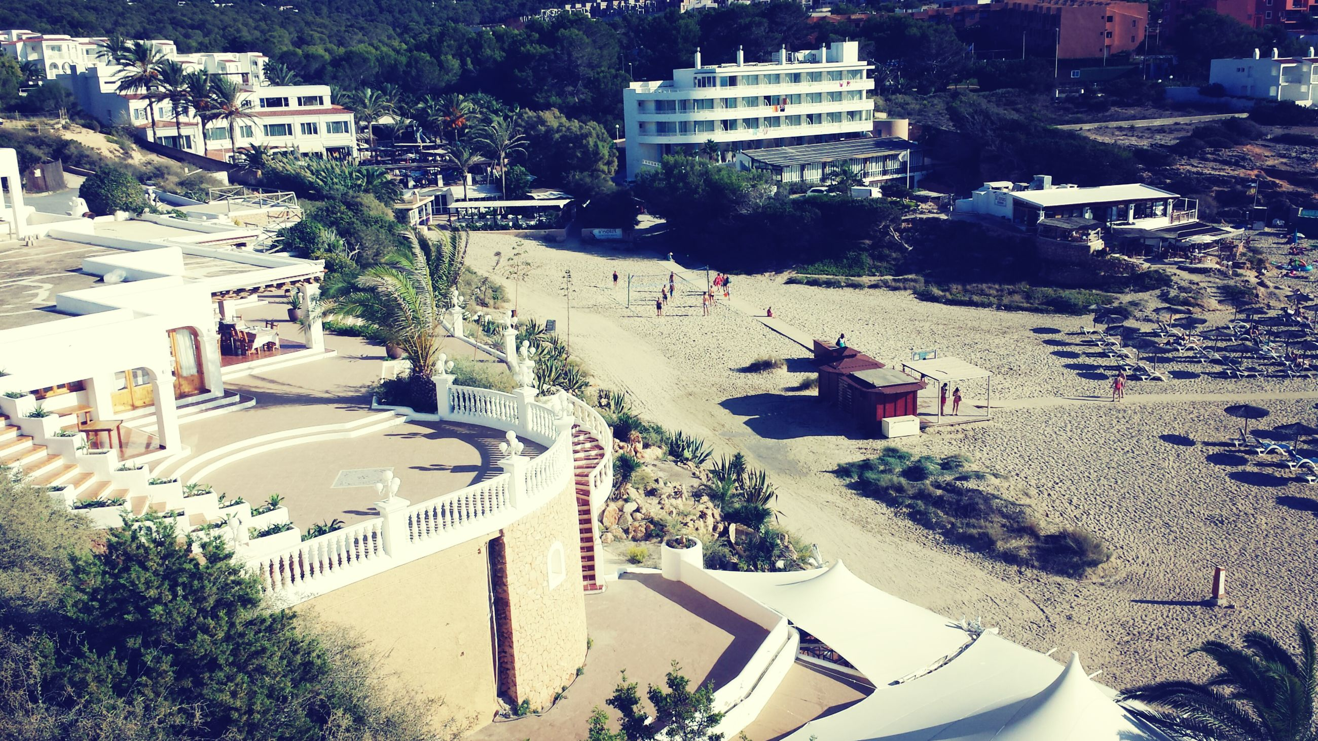 building exterior, architecture, built structure, tree, high angle view, city, incidental people, sunlight, shadow, beach, day, sand, outdoors, house, residential structure, street, leisure activity, travel, city life