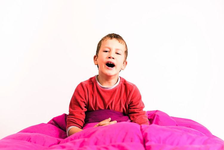 Portrait of boy with toy against white background