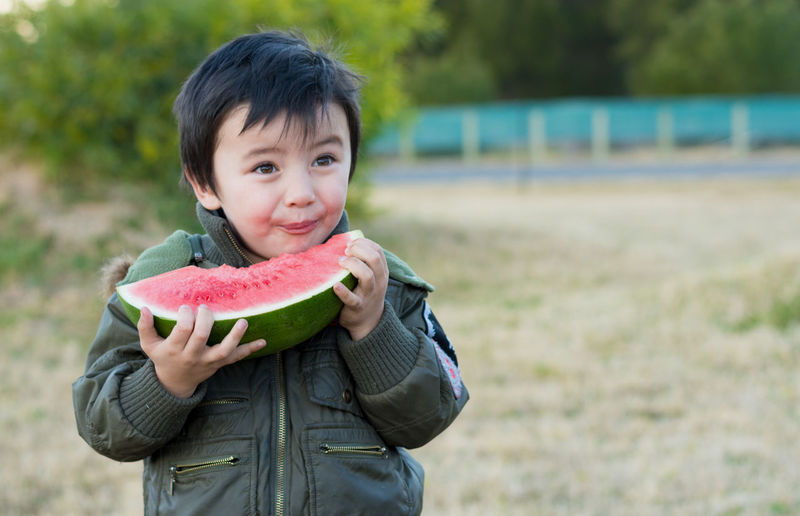 Boy Eating Watermelon While Standing At Park