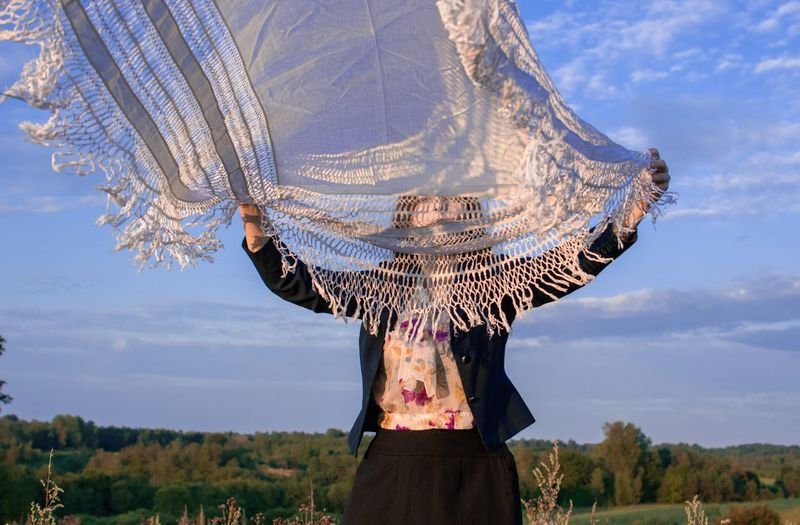 Woman waving textile while standing on field against sky