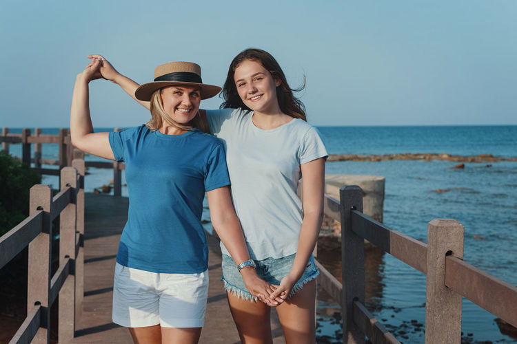 Mother and daughter standing on wooden walkway by the sea
