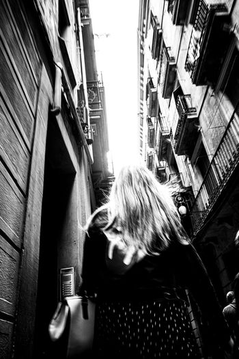Portrait of woman standing by buildings in city