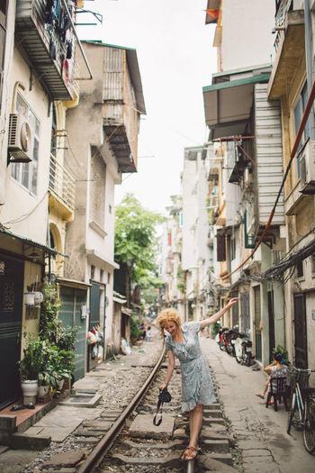 Woman walking on railroad track amidst buildings