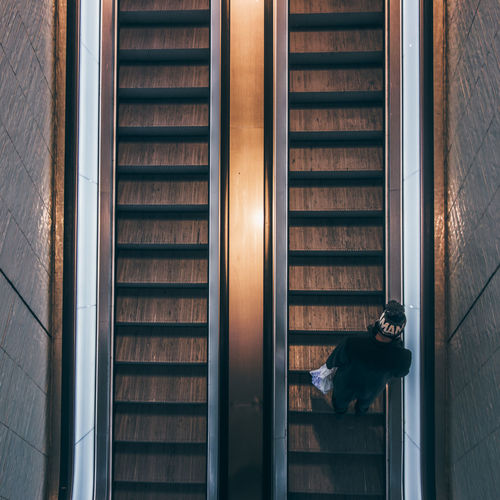 Directly above shot of man on escalator in building