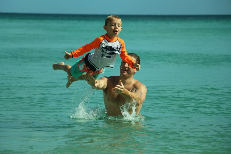 Father And Son Playing In Sea