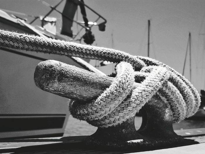 Close-up of rope tied on bollard by boat moored at harbor