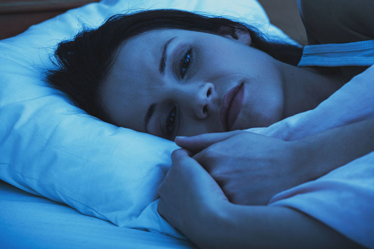 Close-up of portrait of woman sleeping on bed