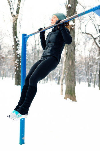 Female Athlete Exercising In Park In Winter With Snow Around The Park Athlete Exercise Lifestyle Nature Running Vertical Composition Winter Active Black Cold Day Female Fit Fitness Motion Nature Outdoors Outside Park Pull Ups Runner Snow Training White Workout