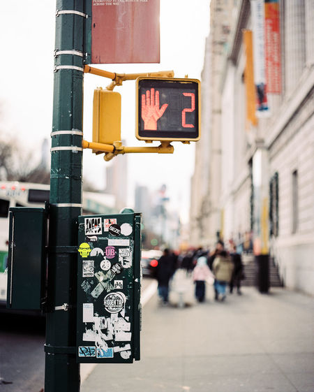 City Focus On Foreground Sign Communication Street Stoplight Road Signal Architecture Incidental People Road Outdoors Day Built Structure Light Guidance Transportation Text Building Exterior City Life City Street Upper West Side Central Park West Cross Walk